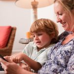 Son using a digital tablet with his mother (Getty Images)